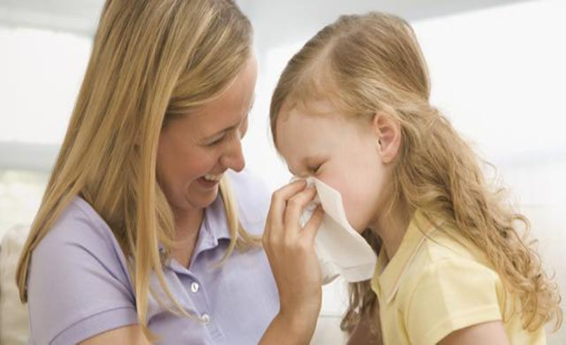 Adult helping child blow their nose